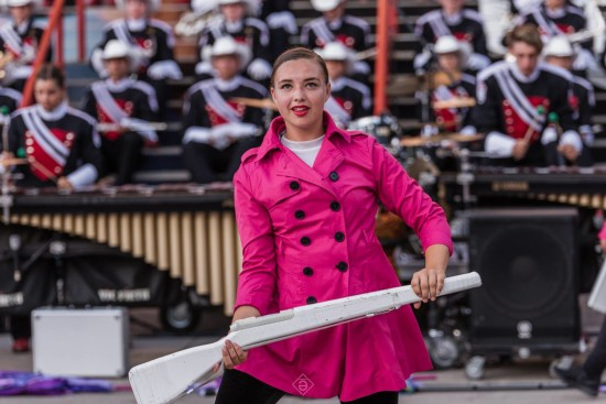 """The Stampede Showband is an auditioned group for youth ages 16-21. Taylor Fraser, pictured here, is preparing to toss her """"rifle"""" into the air, so it'll spin six times, and then catch it. Photo: End Credits"""