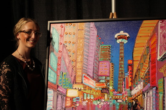 """Pictured: Sheila Kernan and """"My Downtown View."""" Kernan's inspiration comes from her love of Calgary and the way the lights reflect off buildings. She has lived in Calgary for 14 years and is an alumnae of ACAD. Stampede has had a special place in hear heart since 2008 when she was featured as a Rotary Dream  home artist."""