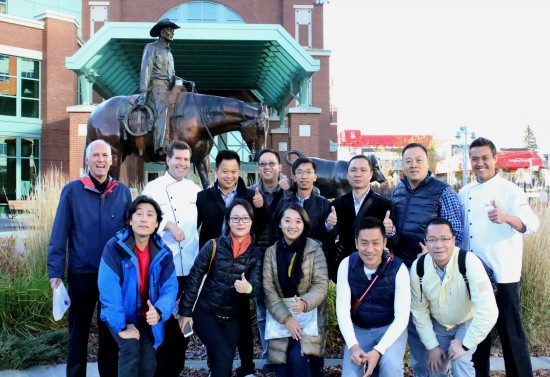 Pictured: (in white jackets) Chef Dale and Chef Kwong making memories with the Chinese tour group and Cargill representatives. Our guests not only got a tour of Stampede facilities, they also got a chance to check out the public art pieces on Stampede Park, like the Roundup, featured behind the group