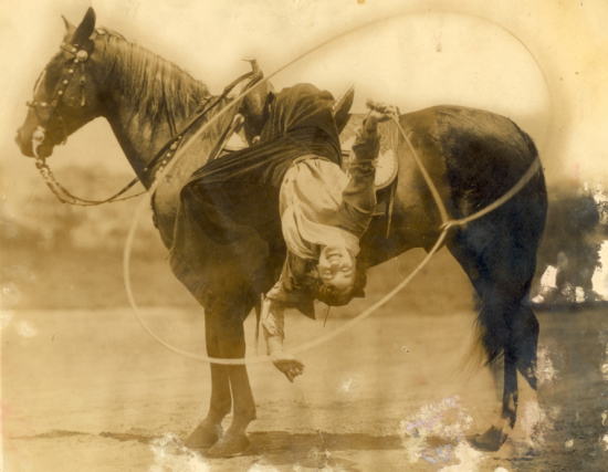 "Flores LaDue hangs from her horse as she shows off her fancy roping skills. Cowgirls had special pants that were made to look like a skirt when they stood, but were in fact pants that enabled them to ride astride. These were called ""split skirts."""