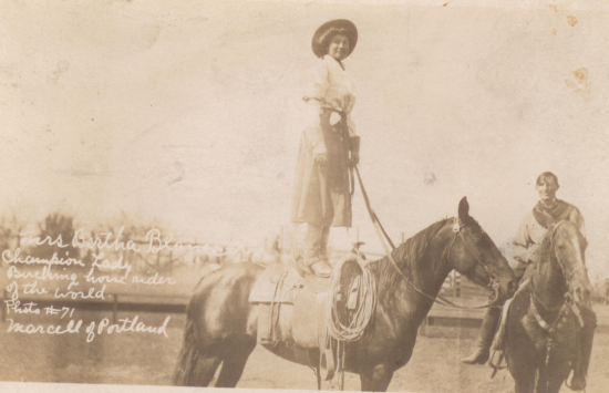 """Bertha Blancett standing on her horse next to her husband, Dell, who was also a rodeo star. Because she is standing, Blancett's """"split skirt"""" looks like a true skirt."""