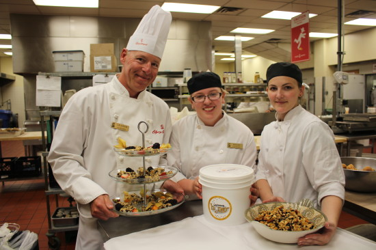 Graham Armstrong, Stampede sous chef, holding the granola bars with his coworkers and fellow chefs holding the honey and granola bits.